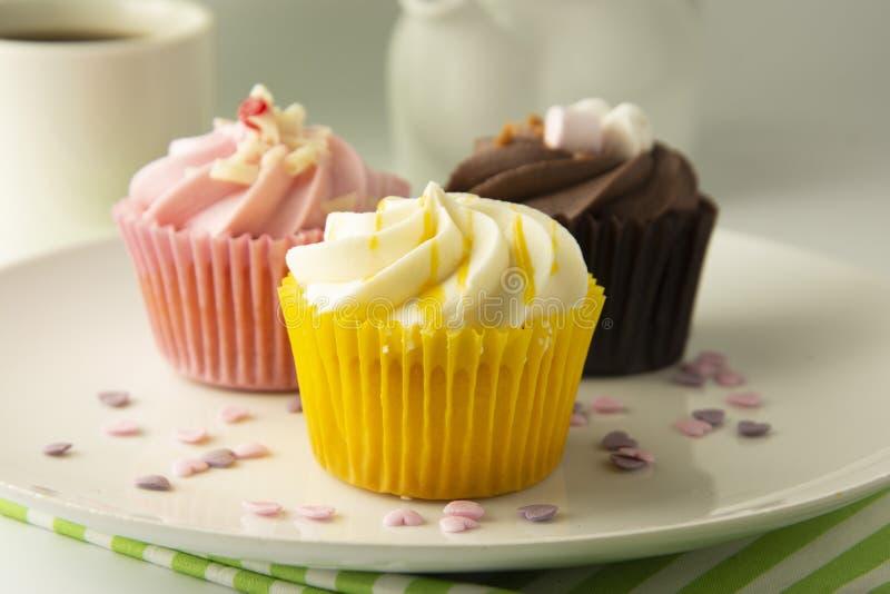 Magdalenas coloridas en un fondo blanco Magdalenas del rosa, amarillas y del chocolate Bocados sabrosos Partido dulce del postre  foto de archivo libre de regalías