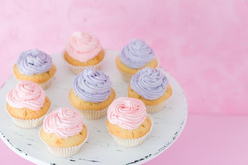 Magdalenas con el buttercream rosado y violeta que se coloca en fondo del rosa en colores pastel imagen de archivo