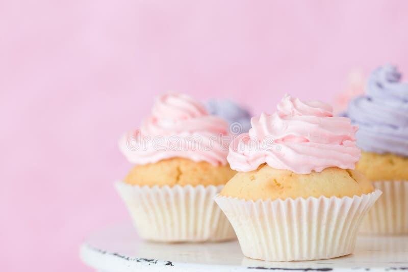 Magdalenas con el buttercream rosado y violeta que se coloca en fondo del rosa en colores pastel imagen de archivo libre de regalías