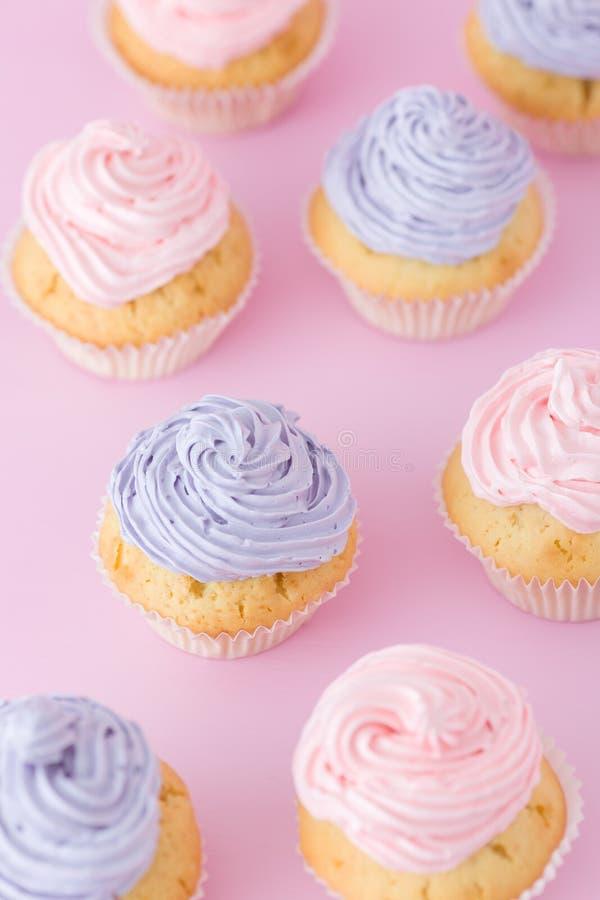 Magdalenas con el buttercream rosado y violeta que se coloca en la opinión superior del fondo del rosa en colores pastel fotos de archivo libres de regalías