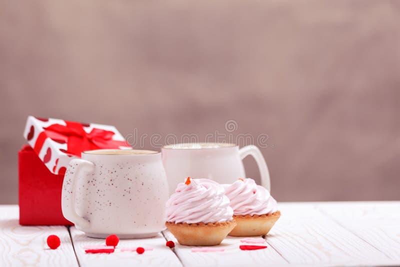 Magdalenas con el primer rosado de las tazas de la crema y de café El concepto del día de tarjeta del día de San Valentín o de cu foto de archivo libre de regalías
