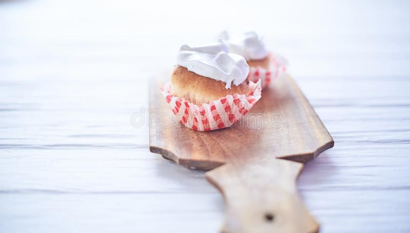 Magdalenas con la crema blanca en un fondo de madera imagenes de archivo