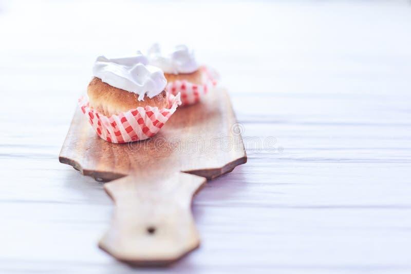 Magdalenas con la crema blanca en un fondo de madera imágenes de archivo libres de regalías