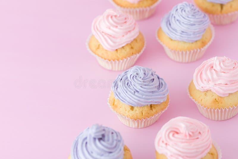 Magdalenas con la crema violeta y rosada que se coloca en la opinión superior del fondo del rosa en colores pastel imagen de archivo