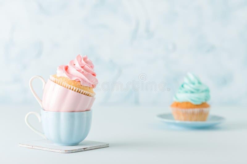 Magdalenas con la decoración poner crema rosada y azul apacible en dos tazas en fondo en colores pastel azul foto de archivo libre de regalías