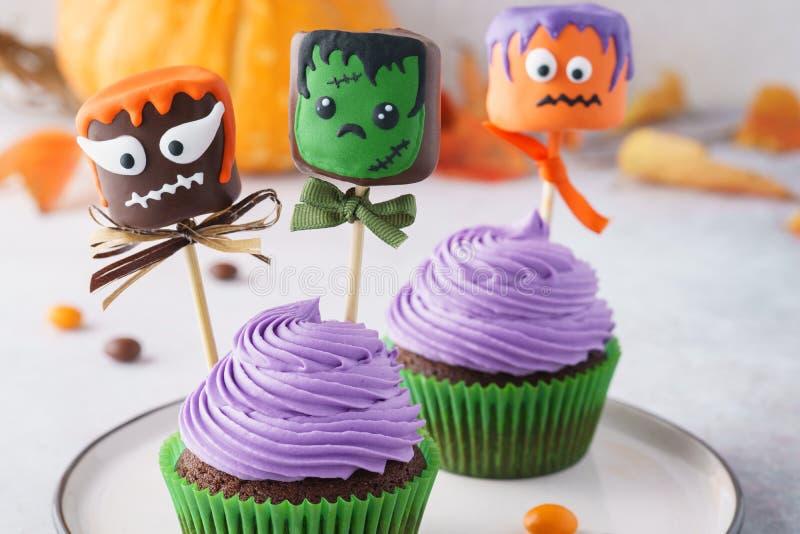 Magdalenas de Halloween adornadas con los monstruos coloridos de la melcocha imágenes de archivo libres de regalías
