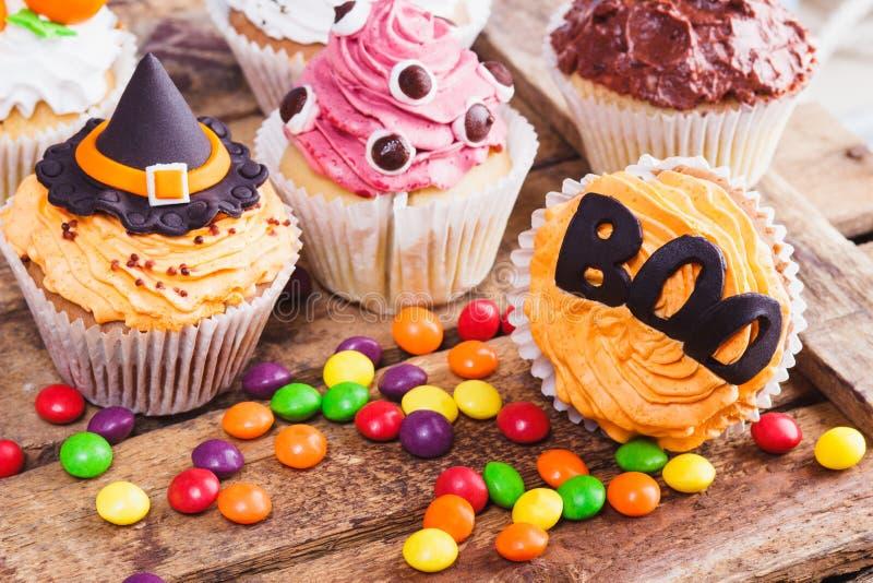 Magdalenas de Halloween con las decoraciones coloreadas fotos de archivo libres de regalías