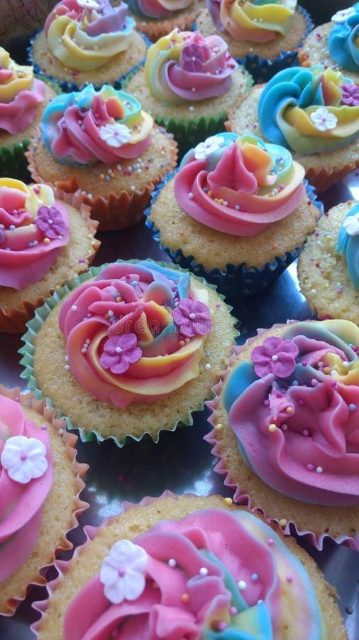 Magdalenas de la fiesta de cumpleaños del arco iris y de la flor fotos de archivo libres de regalías