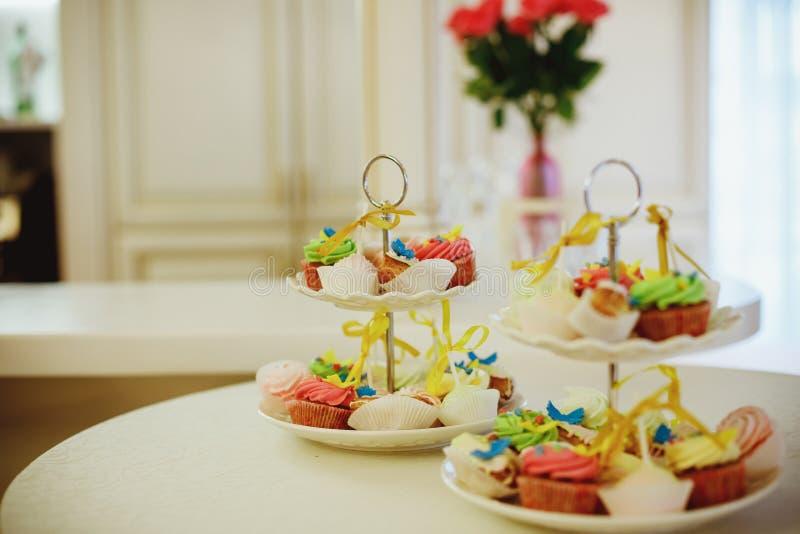Magdalenas de la haba de vainilla mini adornadas con las gotas ciánicas y rosadas del caramelo en una bandeja con gradas clara en foto de archivo libre de regalías