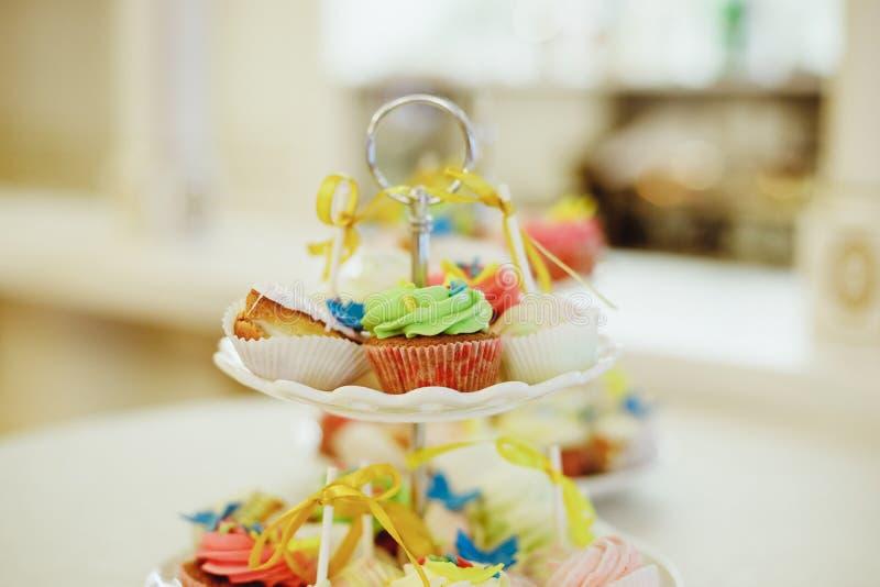 Magdalenas de la haba de vainilla mini adornadas con las gotas ciánicas y rosadas del caramelo en una bandeja con gradas clara en fotografía de archivo libre de regalías