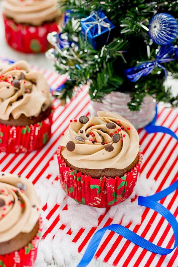 Magdalenas de la Navidad - magdalena del chocolate con helar del buttercream imagen de archivo libre de regalías