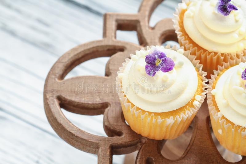 Magdalenas de la vainilla con Sugar Coated Flowers en un soporte de la torta imagenes de archivo