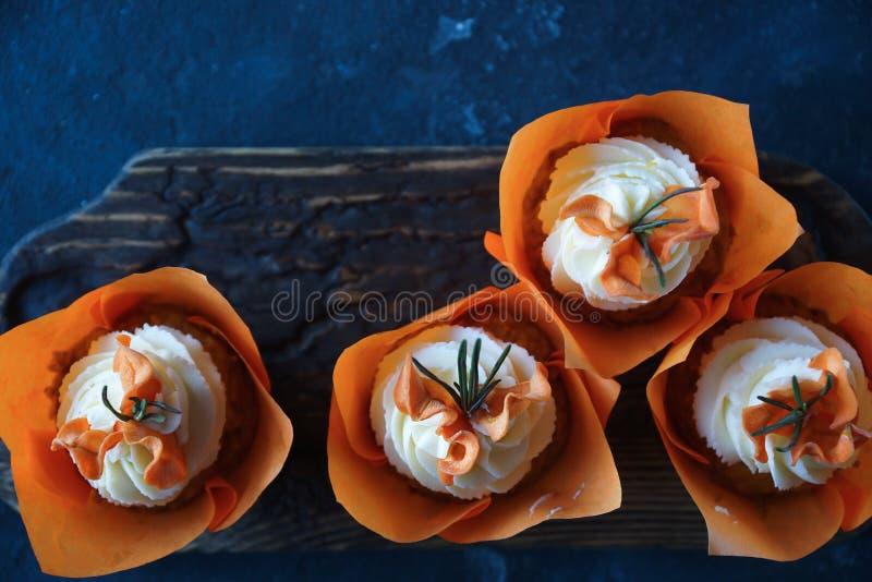 Magdalenas de la zanahoria de Pascua con las naranjas de la crema y del caramelo de la vainilla fotos de archivo