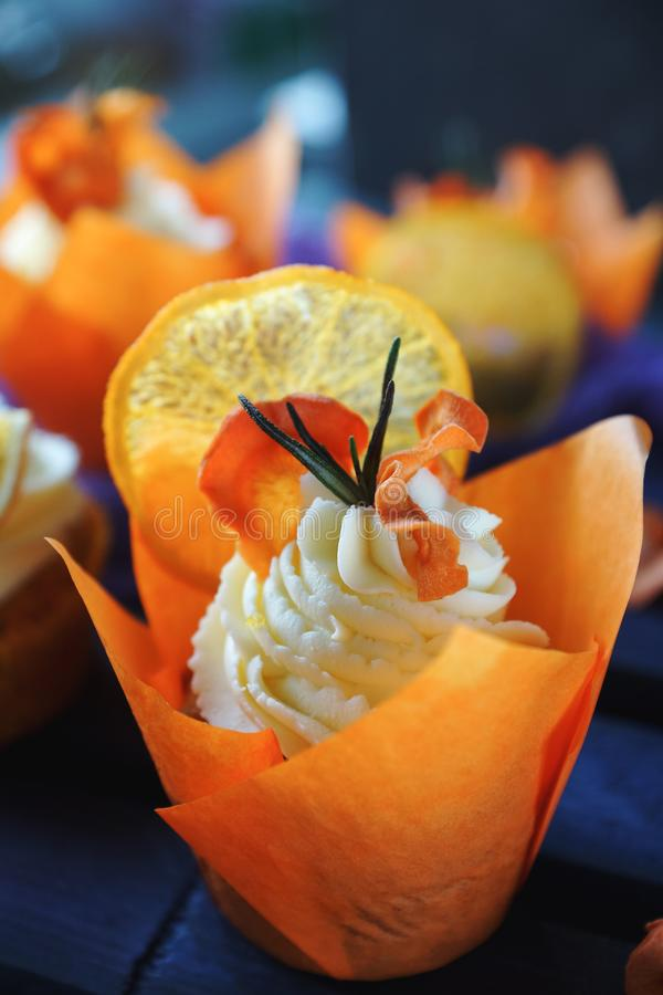 Magdalenas de la zanahoria de Pascua con las naranjas de la crema y del caramelo de la vainilla fotografía de archivo
