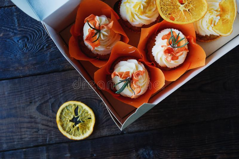 Magdalenas de la zanahoria de Pascua con las naranjas de la crema y del caramelo de la vainilla imagen de archivo