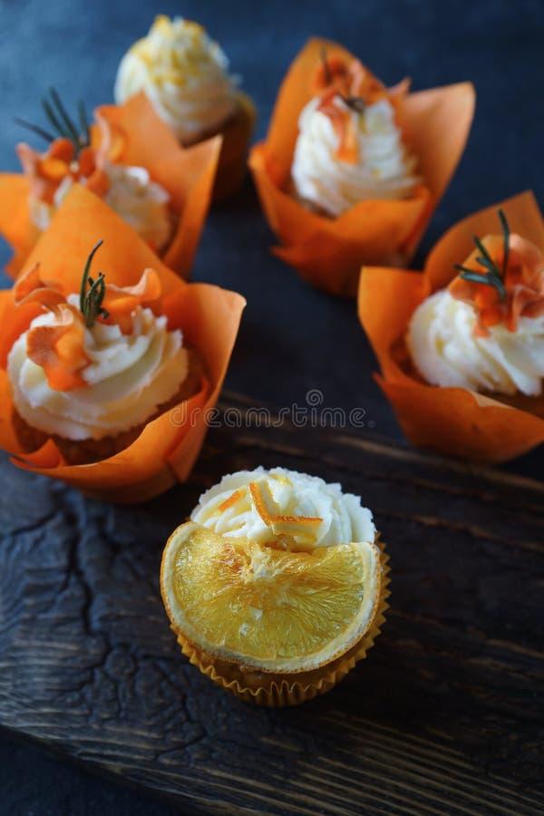 Magdalenas de la zanahoria de Pascua con las naranjas de la crema y del caramelo de la vainilla foto de archivo