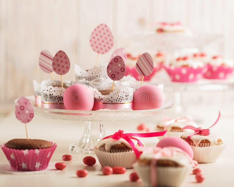 Magdalenas de Pascua adornadas con el caramelo rosado, los huevos de papel y la cinta fotografía de archivo libre de regalías