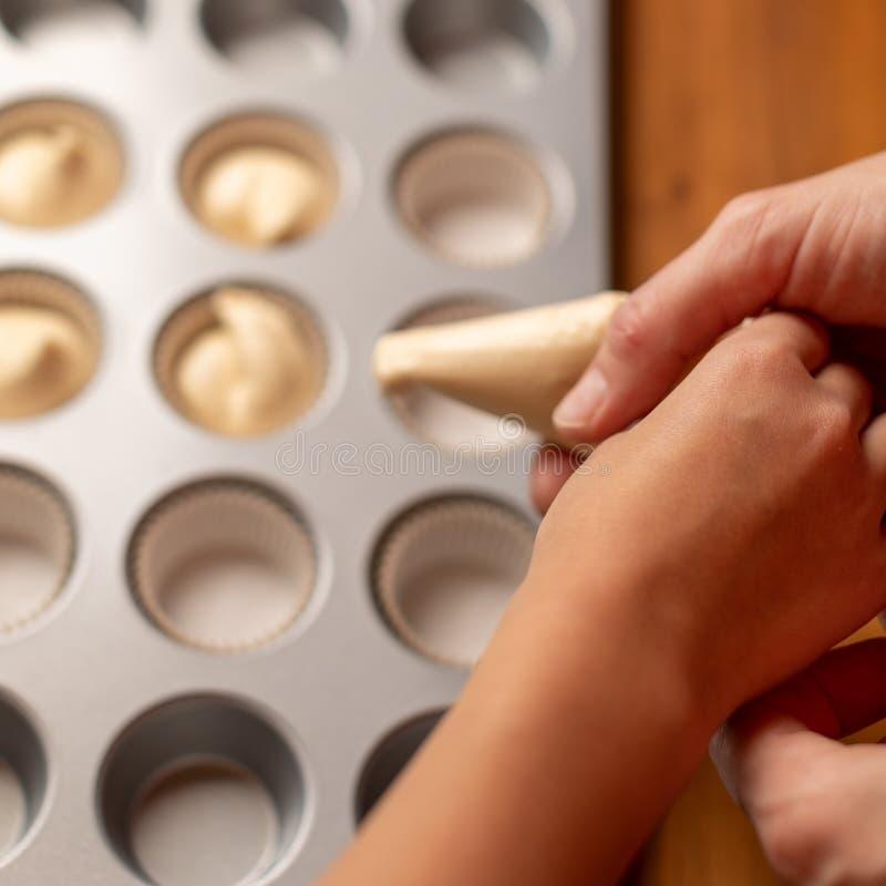 Magdalenas del cocinero de la mamá y de la hija Las mujeres y las manos de los niños exprimen la crema en la forma para las magda foto de archivo