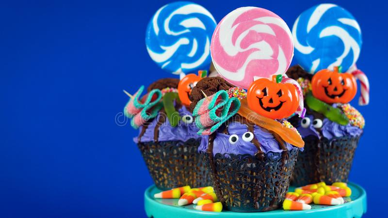 Magdalenas del estilo de la torta del goteo del candyland de Halloween con el caramelo en fondo azul fotos de archivo