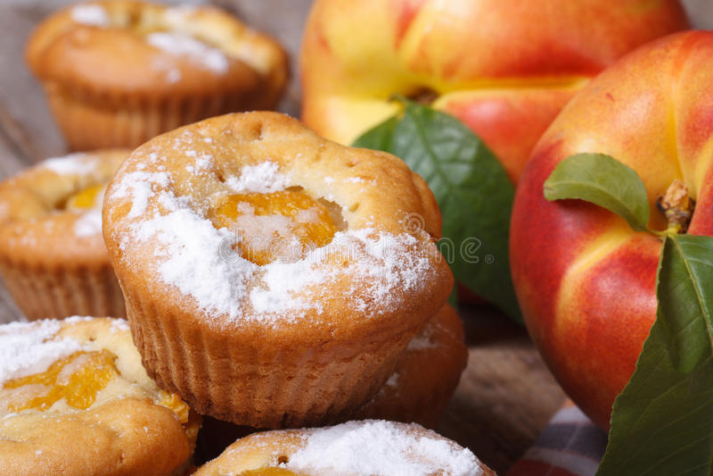 Magdalenas deliciosas con el melocotón asperjado con el azúcar en polvo imagenes de archivo