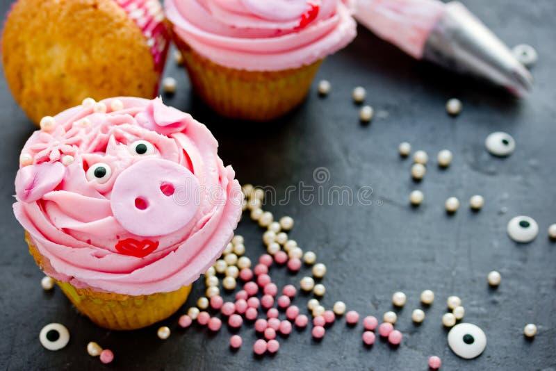 Magdalenas guarras de la Srta. - hermosas y las tortas deliciosas adornadas con crema rosada formó caras guarras divertidas foto de archivo libre de regalías
