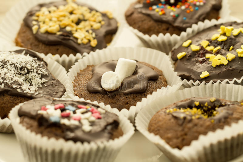 Magdalenas hechas en casa del chocolate adornadas con un desmoche decorativo imagen de archivo libre de regalías