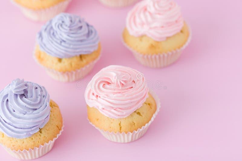 Magdalenas violetas y rosadas con el buttercream que se coloca en fondo del rosa en colores pastel foto de archivo libre de regalías