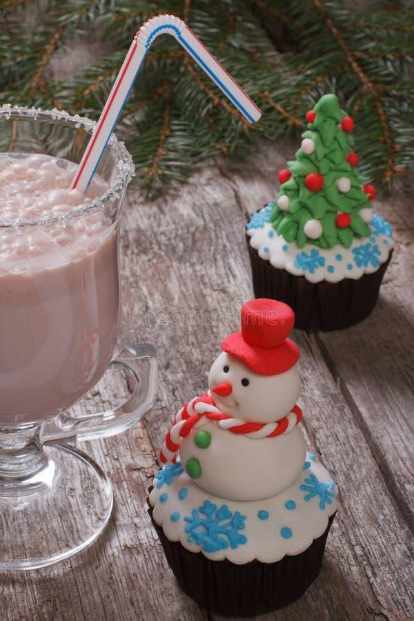 Magdalenas y batidos de leche de la Navidad en un de madera fotografía de archivo