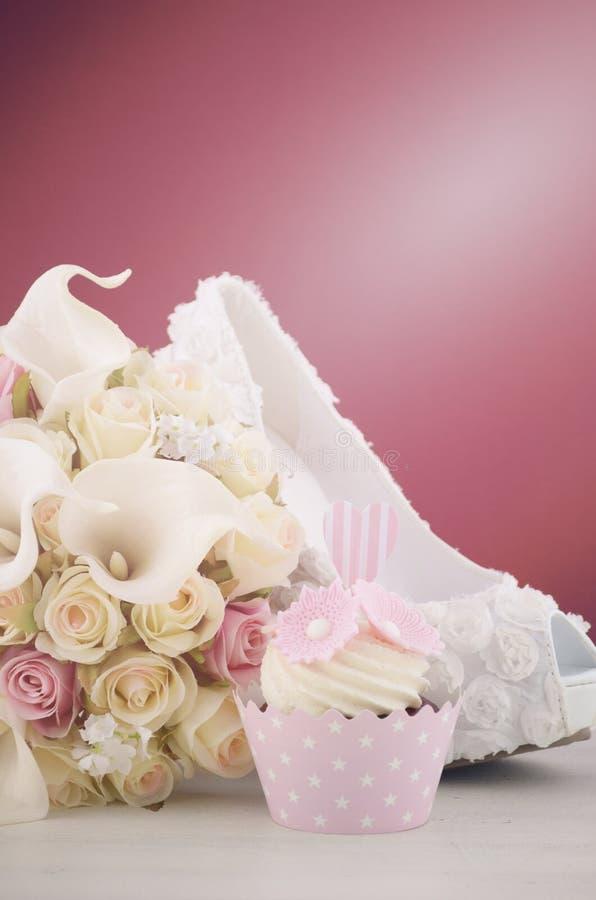 Magdalenas y zapato del concepto de la boda en fondo del marsala fotos de archivo