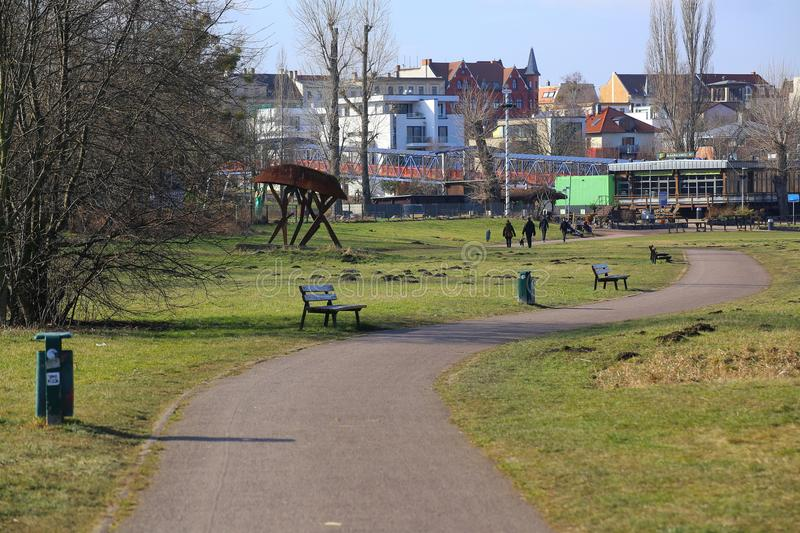 MAGDEBURG, GERMANY - FEB 22 2018 : Meadows along the river Elbe with walking people and sculpture.  stock photo