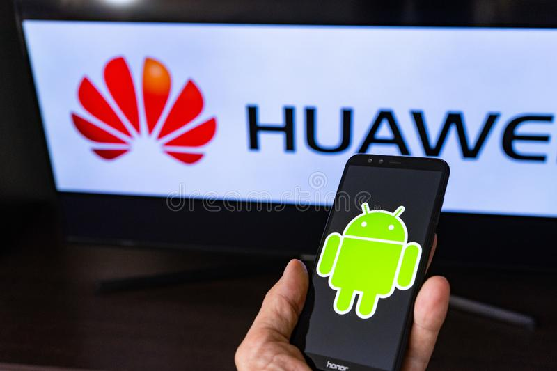 Magdeburg GERMANY - JUNE 2019: a man holding smartphone Honor. On the screen, the Android logo in front of the huawei logo. Google. Restricts Huawei s access to stock image
