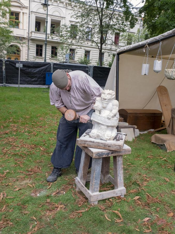 Magdeburg, Germany - 29.08.2014: Kaiser-Otto-Fest. Reconstruction of historical events of the city. Stonemason makes a figure of royalty free stock images