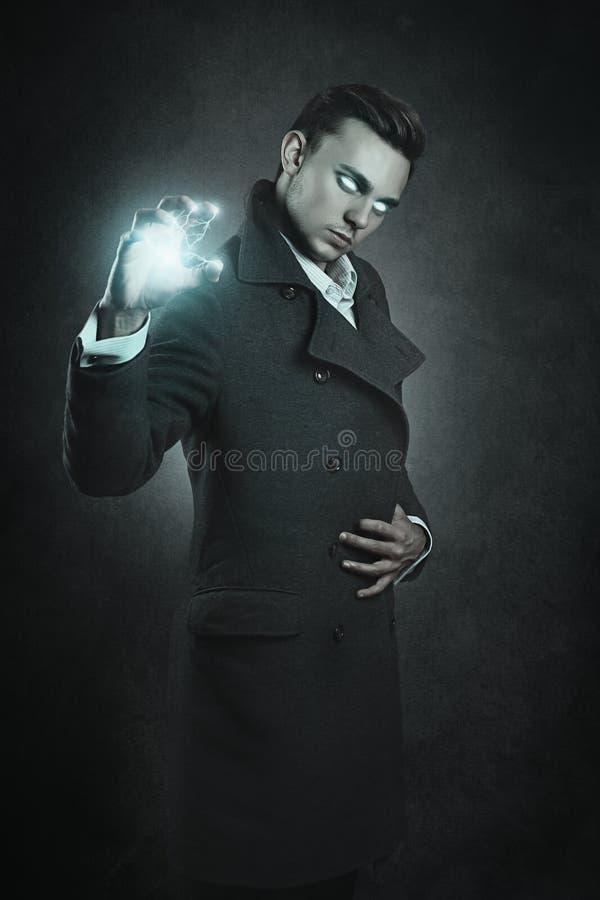 Mage casting thunderbolt. Grey texture background royalty free stock photo