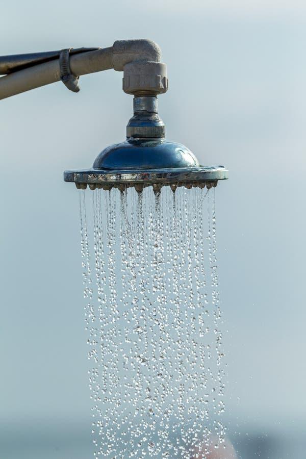 Mage van een uitstekende oude achtergrond van het douche hoofd bespattende water dicht omhoog Waterstromen van het hoofd van een  stock fotografie