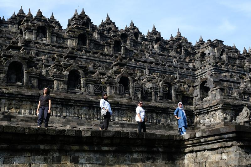 Local women tourists pose at Borobudur Temple. Magelang, Indonesia, 12/04/2019: Local women tourists pose at Borobudur Temple, one of the landmarks that ever stock photo