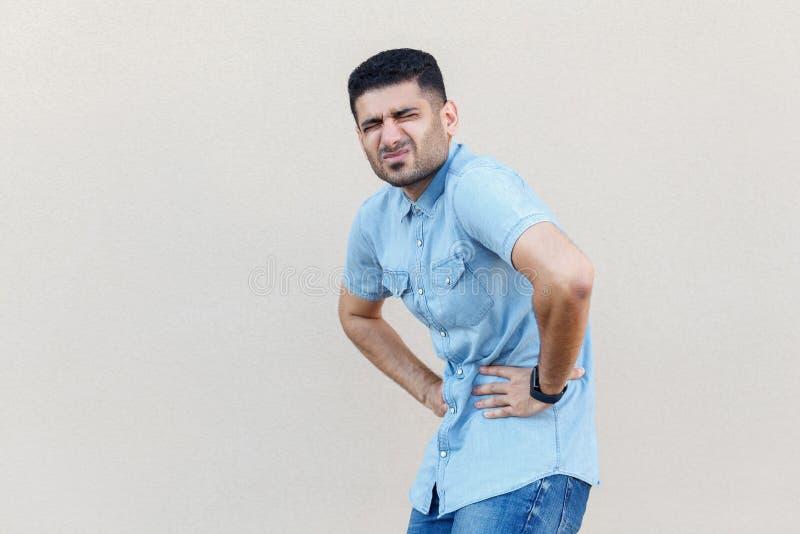 Magen smärtar eller bantar problem Stående av den sjuka stiliga unga skäggiga mannen, i blått anseende och att rymma för skjorta  royaltyfri foto