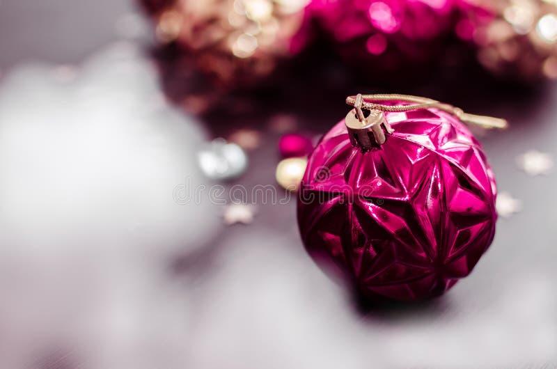 Magenta Kerstmisbal op bokehachtergrond van Kerstmisornamenten stock foto's