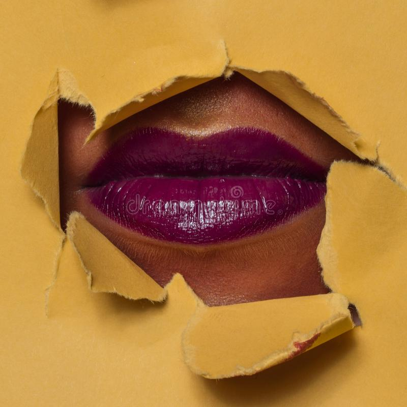 Magenta lips through a hole stock images