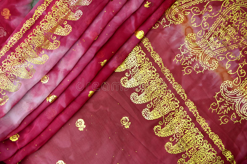 Magenta Pink Indian Sari with Gold Paisley Pattern. Close-up of a vibrant cerise pink tie dye traditional Indian wedding sari garment, with gold paisley and rose royalty free stock images
