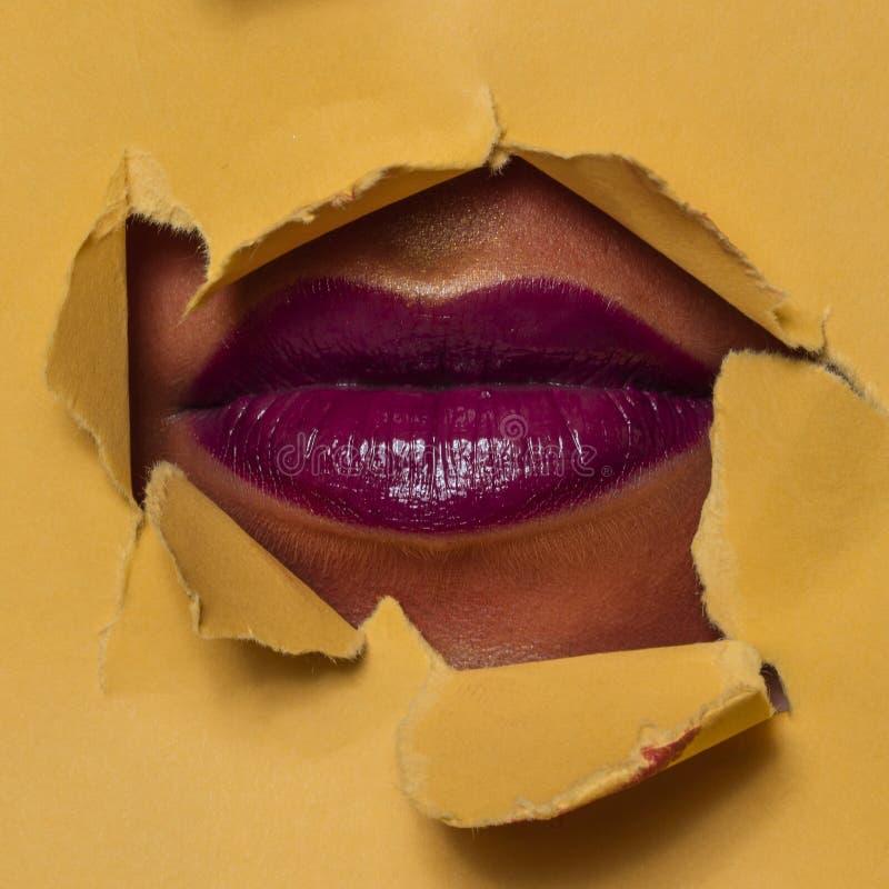 Magentarote Lippen durch ein Loch stockbilder