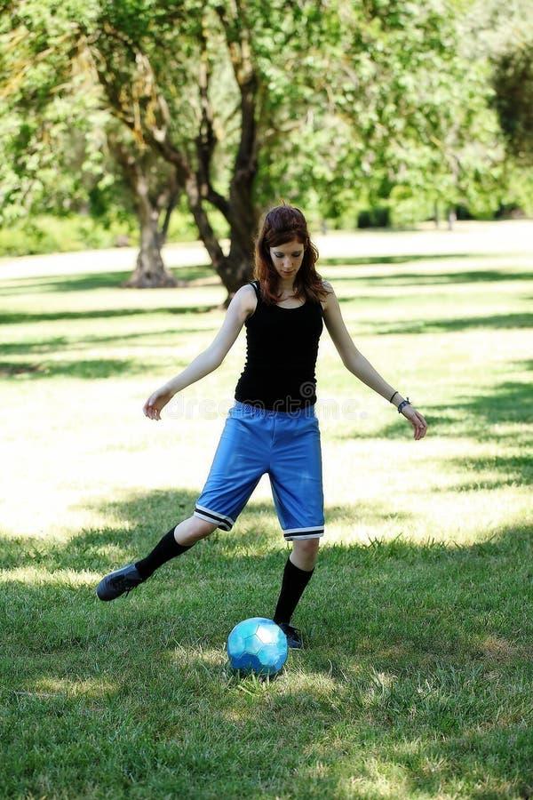 Mager Caucasian tonårig flicka som sparkar den blåa fotbollbollen royaltyfria foton