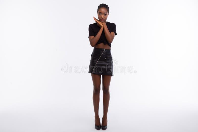 Mager donker-gevild model met lange benen die zwarte leerrok dragen stock foto's