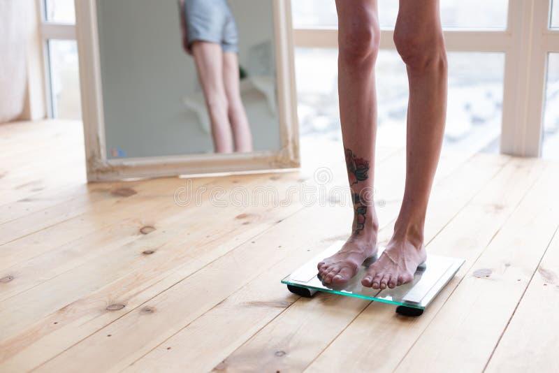 Mager kvinna med tatueringen på benet som står på viktvåg royaltyfria bilder