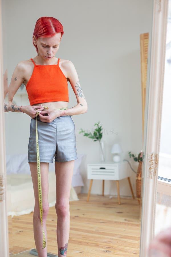 Mager kvinna som mäter hennes midja med måttband arkivfoton