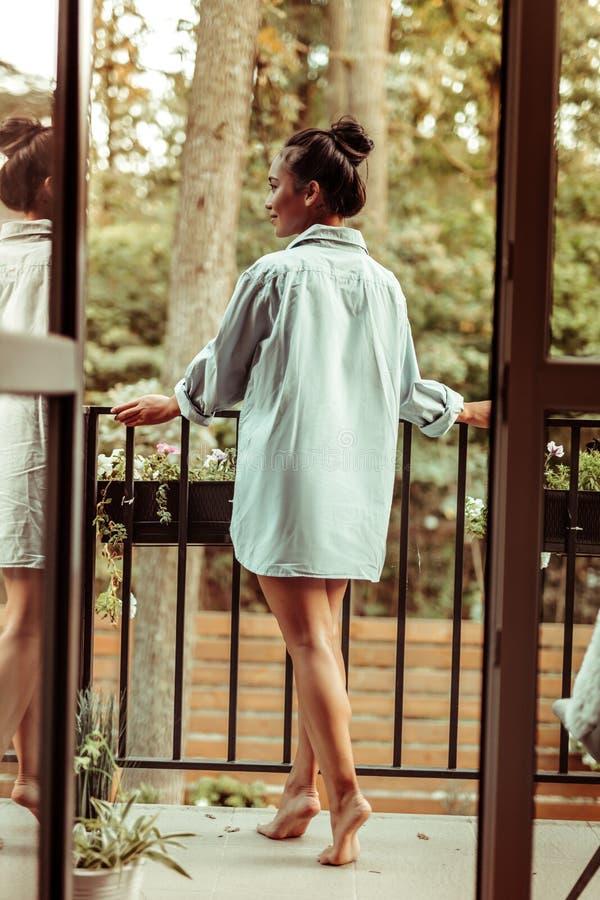 Mager mörker-haired dam i den manliga skjortan observera naturen från en balkong royaltyfria foton