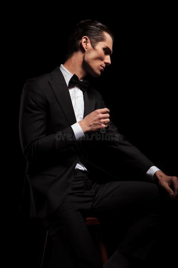 Mager man i svart med bowtie som poserar i mörk studio royaltyfri foto
