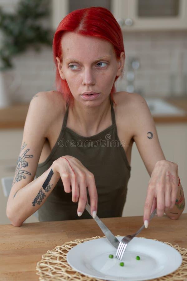 Magere het mes en de vorkzitting van de vrouwenholding dichtbij lege plaat stock foto's
