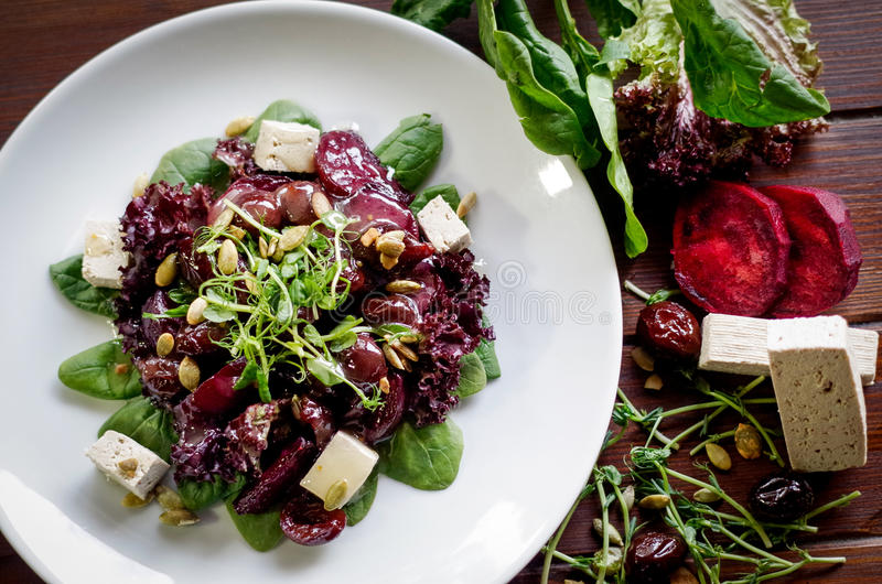 Magere salade, arugula en tofu op een witte plaat met parsl stock afbeelding