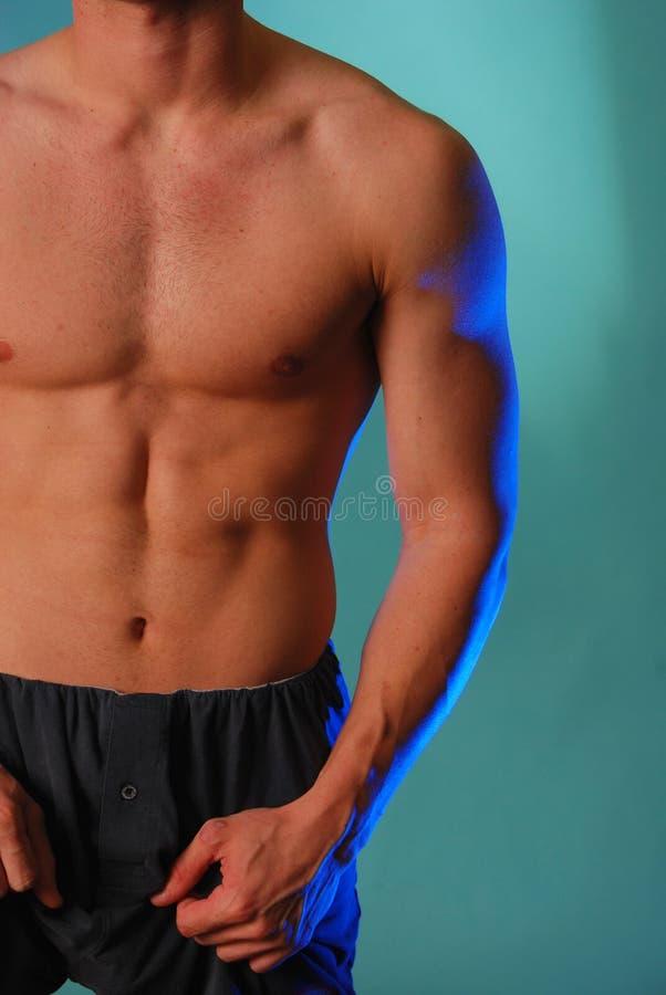 Magerer männlicher Torso im Blau stockfoto