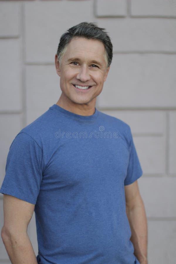 Magerer reifer Mann, der draußen lächelt lizenzfreie stockfotografie